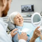 6 Signs You Need New Dentures- dental patient smiling in mirror at their teeth